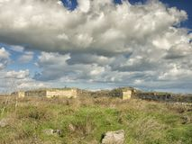 Dramatic blue sky with white clouds over the ruins of the ancient greek colony of Histria, on the shores of Black Sea. Histria is Royalty Free Stock Photography