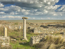 Dramatic blue sky with white clouds over the ruins of an ancient greek column at Histria, on the shores of Black Sea. Histria is t. He oldest urban settlement on Royalty Free Stock Image