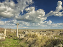 Dramatic blue sky with white clouds over the ruins of an ancient greek column at Histria, on the shores of Black Sea. Histria is t Stock Photos