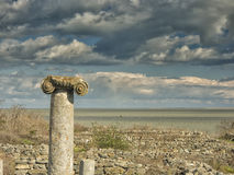 Dramatic blue sky with white clouds over the ruins of an ancient greek column at Histria, on the shores of Black Sea. Histria is t Royalty Free Stock Photos