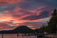 Dramatic pink and blue sunset with a round hill, boat and doc from Lakeside Beach at Lake Tahoe. Dramatic bright pink and blue sunset with a round hill, boat and royalty free stock images