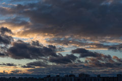 Dramatic cityscape and cloudscape in sunset time with heavy clouds on sky Royalty Free Stock Photography