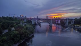 A wide angle long exposure of Minneapolis bridges spanning the Mississippi River in front of the Downtown Skyline during Sunset stock video