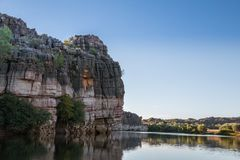 Dramatic cliffs against a bright sky. Darngku cliffs reflected in calm Fitroy River water Royalty Free Stock Photography