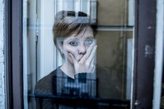 Dramatic close up portrait of young beautiful woman thinking and feeling sad suffering depression at home window looking depresse. D and worried in lifestyle and royalty free stock image