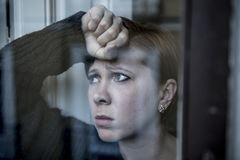 Dramatic close up portrait of young beautiful woman thinking and feeling sad suffering depression at home window looking depresse. D and worried in lifestyle and royalty free stock photos