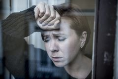Dramatic close up portrait of young beautiful woman thinking and feeling sad suffering depression at home window looking depresse. D and worried in lifestyle and royalty free stock photography