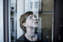 Dramatic close up portrait of young beautiful woman thinking and feeling sad suffering depression at home window looking depresse. D and worried in lifestyle and stock photo