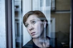 Dramatic close up portrait of young beautiful woman thinking and  feeling sad suffering depression at home window looking depresse Royalty Free Stock Photos