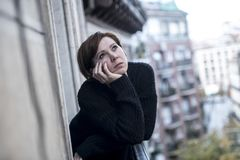 Young beautiful woman thinking and feeling sad suffering depression at urban city background home balcony Stock Photo