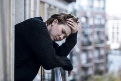 Young beautiful woman thinking and feeling sad suffering depression at urban city background home balcony Stock Images