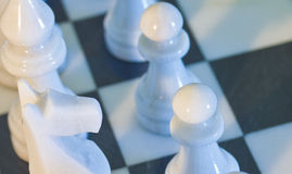Dramatic closeup of chess board. And pieces. Metaphor for teamwork, success, planning and contest.  Shallow depth of field Stock Photography