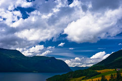 Dramatic clouds. Over Norwegian fjord, fields and mountains Royalty Free Stock Photos