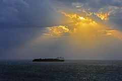 Dramatic Clouds. Dramatic sunset with the sun behind the clouds and a big container ship on the sea Royalty Free Stock Photos
