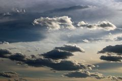 Dramatic clouds against a mainly grey sky. View of dramatic clouds in a predominantly grey sky with sunlight backlighting the clouds stock photography