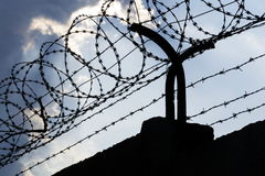 Dramatic clouds behind barbed wire fence on prison wall Royalty Free Stock Photography