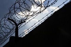 Dramatic clouds behind barbed wire fence on prison wall. Dramatic clouds behind barbed wire fence on a prison wall Royalty Free Stock Photography