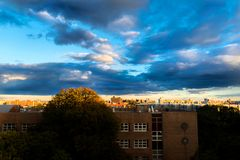 Dramatic clouds moving across a blue sky, while the setting sun adds a golden glow to the urban setting, Bronx, NY, USA. Dramatic clouds moving across a blue sky royalty free stock photos