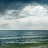 Dramatic clouds over darken sea Stock Photography