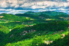 Dramatic clouds over green hills. And village houses. Samobor town suburb, Croatia Stock Photo