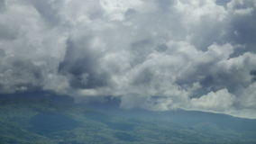Dramatic clouds over hills and mountains in Tuscany Italy. Static medium long high angle high dynamic range shot of dramatic cumulus clouds above rolling hills stock video footage