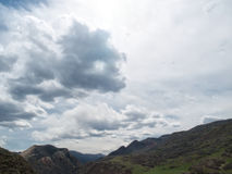 Dramatic clouds over a mountain landscape. A variety of dramatic clouds fill the sky over a desert mountain landscape Royalty Free Stock Images