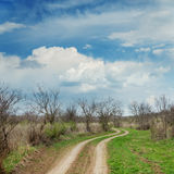 Dramatic clouds over winding road in spring meadow Royalty Free Stock Photography