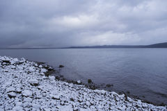 Dramatic clouds over winter lake scene with snowy shore Stock Photos