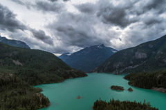 Dramatic clouds roll over Diablo Lake, North Cascades National Park, Washington. Clouds roll over green Diablo Lake in North Cascades National Park, Washington Royalty Free Stock Photos