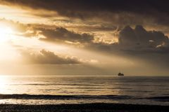 Sun rays flowing over ship on the horizon in Larnaca Royalty Free Stock Photos