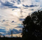 Dramatic clouds silhouettes trees high-voltage tower royalty free stock photos