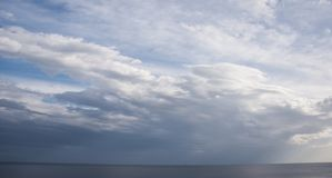 Dramatic clouds and sky over the ocean. With a lonely boat in the background. Blue and white beautiful scene royalty free stock photography