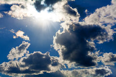 Dramatic clouds and sunbeams on blue sky Royalty Free Stock Images