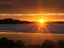 Dramatic clouds and sunset over lake in Bemidji Minnesota. Sunset over Lake in Bemidji Minnesota that is mostly covered with ice in early spring scene with royalty free stock photography