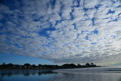 Dramatic clouds suspended over New England beach Royalty Free Stock Images