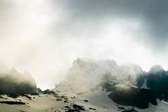 Dramatic clouds on top of snowy mountain stock photography