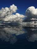 Dramatic Cloudscape. On a blue sky, reflecting in the ocean Stock Image