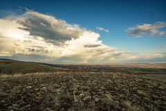 Dramatic cloudscape near Bulgarian village. Village in valley on cloudy rainy day. Panoramic landscape of village with multi colored roofs Stock Photo