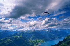 Dramatic cloudscape over mountains. And lake with paraglider silhouette. Swiss alps over Walensee Stock Photos