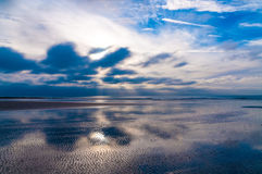 Dramatic cloudscape reflecting on coastline in Cote d'Opale in France Stock Photo