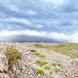 Dramatic cloudscape on stone desert with see afar Royalty Free Stock Images