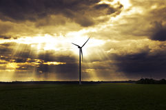 Dramatic cloudscape with sun rays and wind power plant - before Stock Image