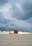Dramatic cloudy minimalist beach view with a wooden dressing cabin. changing room. Dramatic cloudy minimalist beach view with a wooden dressing cabin royalty free stock images