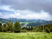 Dramatic cloudy misty mountain ladscape, meadow and forest. Dramatic cloudy misty landscape. mountain meadow and forests, both deciduous broadleaved and needle Royalty Free Stock Images
