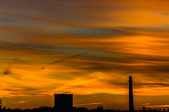 Dramatic cloudy orange sky with city silhouette Stock Images