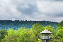 Dramatic cloudy over the tropical forest and animal watching tower hideout. Summer scene in Ta Phraya National Park, Thailand. UNESCO world heritage site royalty free stock photo
