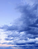 Dramatic cloudy sky at sunset. Dramatic blue cloudy formations in sky at sunset royalty free stock photography