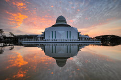 Dramatic cloudy sunrise over white floating mosque. Royalty Free Stock Photography