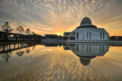 Dramatic cloudy sunrise over white floating mosque. Royalty Free Stock Photos