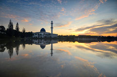 Dramatic cloudy sunrise over white floating mosque. Stock Photography